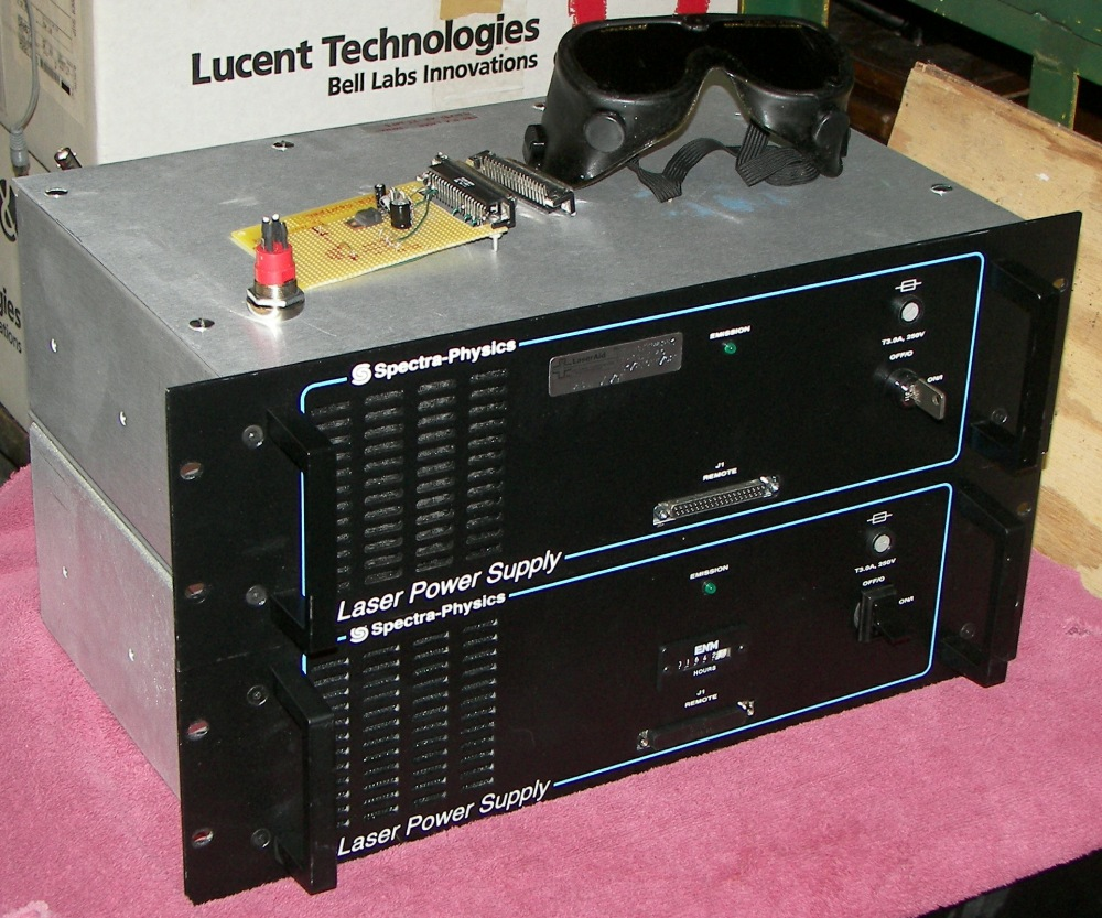 A pair of R2-series power supplies (diode pumps). Only one is used at a  time, the other is a spare. Note the laser goggles. Only a fool uses  invisible laser ...